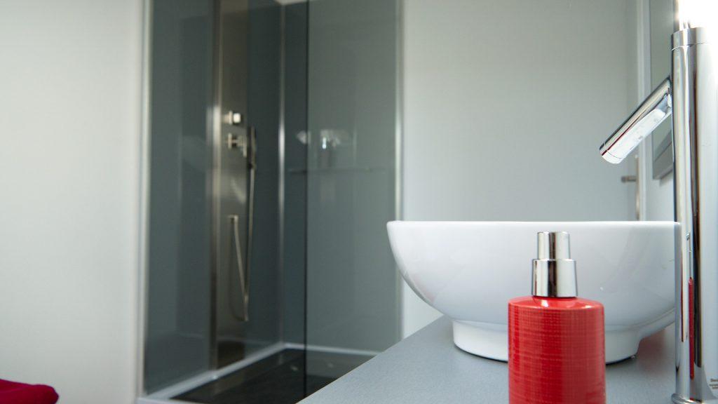 Lavabo et douche dans la salle de bain de la chambre 16